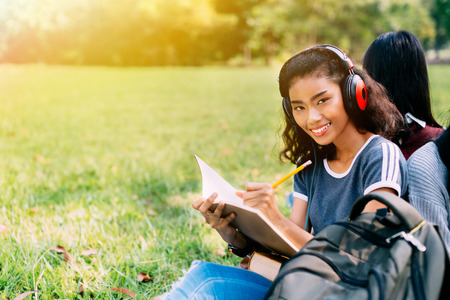Half African American and Asian young and happy smiling woman wearing headphone and working songwriting and composing music related works in outdoors park