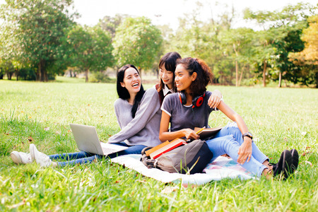 Happy and smiling mixed diverse racial female student friends lying down on grass while using a computer laptop together in park