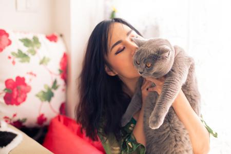Młoda azjatycka piękna właścicielka trzyma i całuje własnego uroczego brytyjskiego kota krótkowłosego w pokoju