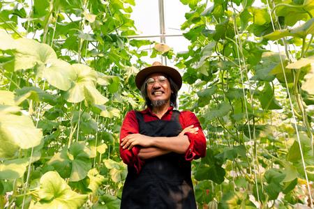 Älterer männlicher Bauer mittleren Alters, der im Sommer die Arme mit einem glücklichen zähneknirschenden Lächeln verschränkt hat und einen Strohhut in roter Landwirtschaftsuniform im Bauerngarten trägt Standard-Bild