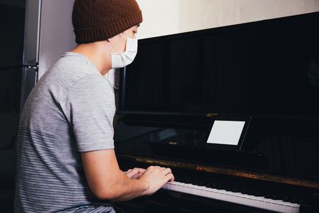 Young Asian male patient with sickness playing piano while using an empty copy space tablet screen at home - Telecommunication Healthcare  and music therapy concept Stock Photo
