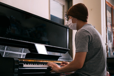 Young Asian male patient with sickness playing piano while using an empty copy space tablet screen at home - Telecommunication Healthcare  and music therapy concept Фото со стока