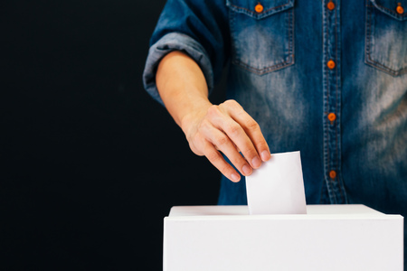 Vista frontale della persona in possesso di scheda elettorale che esprime il voto in un seggio elettorale per il voto elettorale in sfondo nero