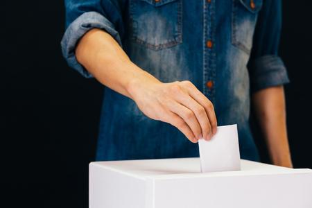 Widok z przodu osoby trzymającej kartę do głosowania, która oddaje głos w lokalu wyborczym do głosowania wyborczego na czarnym tle