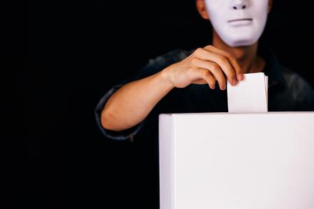 Masked criminal holding ballot paper casting fake vote at a polling station for election vote in black background