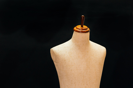 Old and vintage mannequin made of cloth standing in black background lid in 3d - can be used for tailoring and garment concept