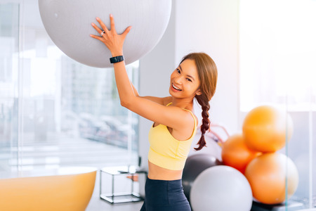 Portrait de jeune femme asiatique en forme tenant un ballon suisse d'exercice et souriant à la caméra. Image modèle de fitness féminin animé