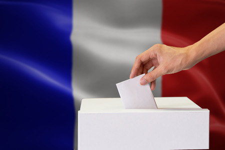 Close-up of human hand casting and inserting a vote and choosing and making a decision what he wants in polling box with France flag blended in background