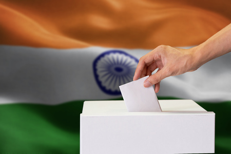 Close-up of human hand casting and inserting a vote and choosing and making a decision what he wants in polling box with India flag blended in background