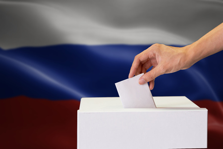 Close-up of human hand casting and inserting a vote and choosing and making a decision what he wants in polling box with Russia flag blended in background