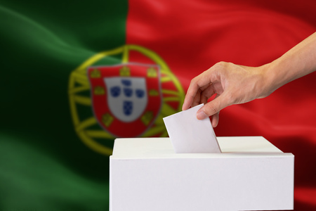 Close-up of human hand casting and inserting a vote and choosing and making a decision what he wants in polling box with Portugal flag blended in background