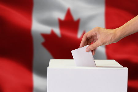Close-up of human hand casting and inserting a vote and choosing and making a decision what he wants in polling box with Canada flag blended in background 스톡 콘텐츠 - 116539970