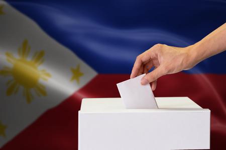 Gros plan sur une main humaine jetant et insérant un vote et choisissant et prenant une décision ce qu'il veut dans l'urne avec le drapeau des Philippines mélangé en arrière-plan. Banque d'images