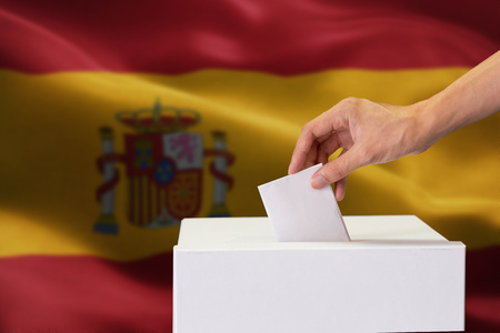 Close-up of human hand casting and inserting a vote and choosing and making a decision what he wants in polling box with Spain flag blended in background
