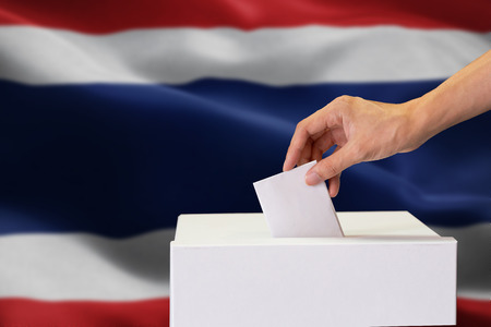 Close-up of human hand casting and inserting a vote and choosing and making a decision what he wants in polling box with Thailand flag blended in background Stock Photo
