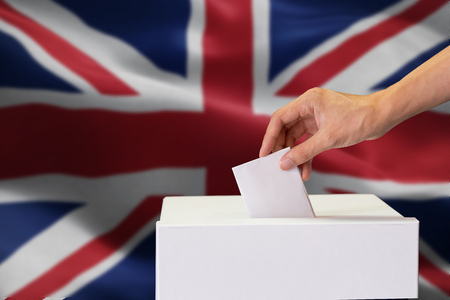 Close-up of man casting and inserting a vote and choosing and making a decision what he wants in polling box with United Kingdom or UK flag blended in background. Imagens - 116539976