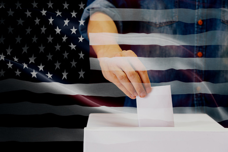 Close-up of man casting and inserting a vote and choosing and making a decision what he wants in polling box with United States flag blended in background Stock Photo