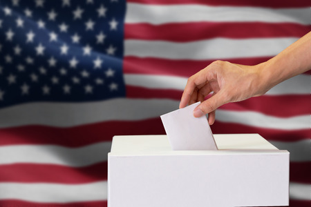 Close-up of man casting and inserting a vote and choosing and making a decision what he wants in polling box with United States flag blended in background.. Stock Photo