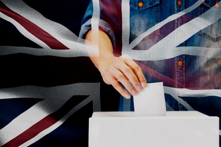 Close-up of man casting and inserting a vote and choosing and making a decision what he wants in polling box with United Kingdom or UK flag blended in background.