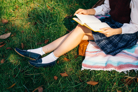 Close-up of woman wearing school college uniform with scotland pleated skirt and reading a book in nature green grass park