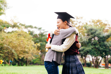 Smiling and happy Asian female graduate student hugging and embracing people with graduation hat in nature park