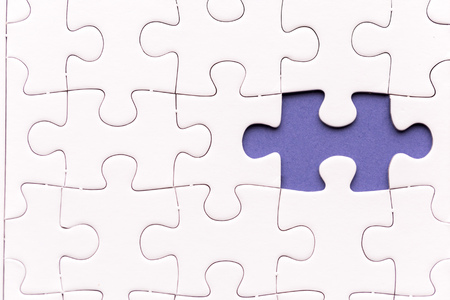 Unfinished white jigsaw puzzle pieces. One missing jigsaw piece on purple background Standard-Bild - 116599915