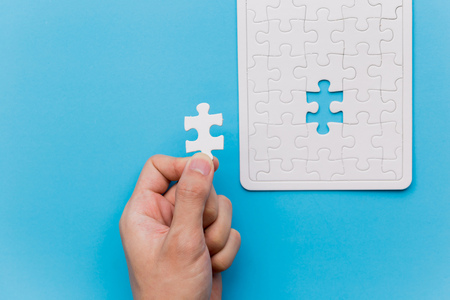 Hands holding one last piece of jigsaw puzzle in blue background with unfinished white jigsaw puzzle pieces