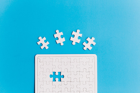 Unfinished white jigsaw puzzle pieces. One missing jigsaw piece on blue background Stock Photo