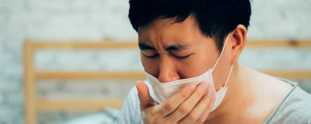 Young Asian man coughing and suffering in medical mask inside home bedroom - illness and fever concept - with copy space banner size