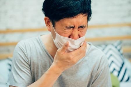 Junger asiatischer Mann hustet und leidet in medizinischer Maske im Schlafzimmer zu Hause - Krankheits- und Fieberkonzept