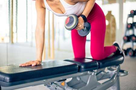 Close up of young Asian active fit woman in sportswear with concentration raising and pulling dumbbells with one hand on bench inside gym
