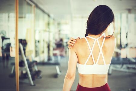 Cerca de joven deportista asiática muscular y activa que tiene tensión en el hombro durante el gimnasio de entrenamiento en el interior