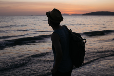 One young male travel thoughtful and calm backpacker looking towards the sea and thinking of journey. Stock fotó