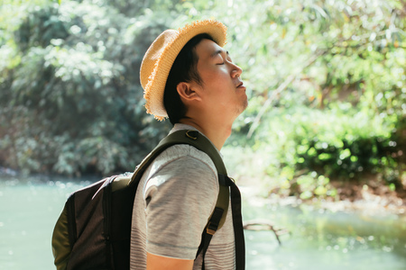 Young Asian male traveler enjoying and inhaling healthy air in green nature forest - fresh air and life wellbeing.