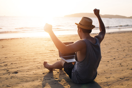 Young male businessman putting hands up for success on tropical summer beach - it indicates freedom such as financial freedom or remote work concept.