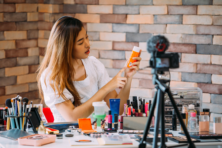 Charming Asian girl recording vlog. Beauty blogger presenting makeup cosmetics in front of camera Stock Photo