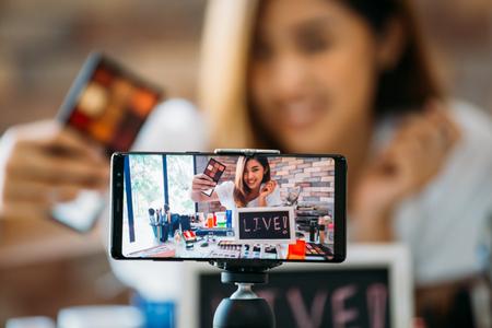 Heureux jeune modèle ethnique asiatique séduisant filmant un vlog sur un téléphone portable sur un trépied et montrant des ombres à paupières à table avec des cosmétiques Banque d'images