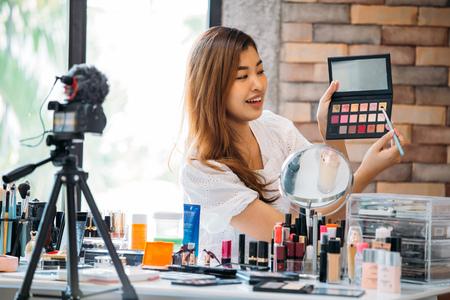 Mujer bonita asiática grabando video tutorial de maquillaje sobre cosméticos con teléfono móvil en trípode. Foto de archivo