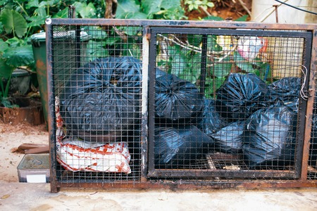 Plastic bags with garbage placed inside rusty metal cage on sunny day in countryside