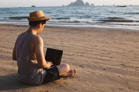 Back view of barefoot man in hat sitting on sandy beach near waving sea and browsing modern laptop Stock Photo