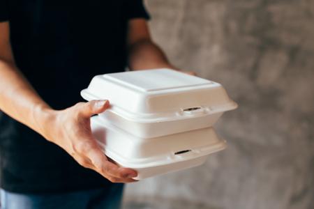 Close-up van bezorger die een stuk schuimlunchdoos overhandigt - Schuimdoos is giftig plastic afval. Gebruikt voor recycling en milieubesparend concept; Stockfoto