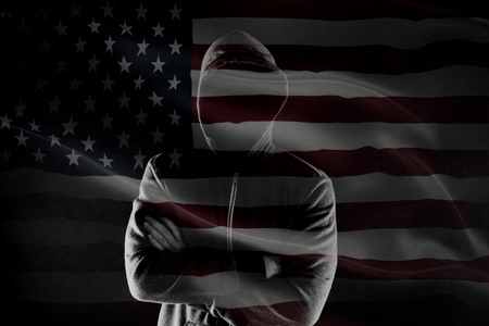 Double exposure of concept of criminal in USA with silhouette of male with crossed hands in hood and flag Archivio Fotografico