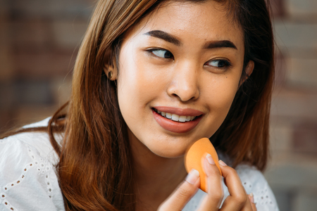Closeup young Asian positive woman applying powder on shiny face on blurred background