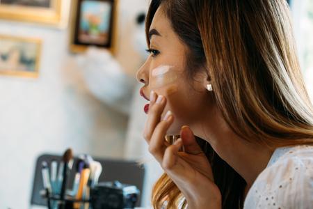 Zbliżenie młoda Azjatycka kobieta z czerwonymi ustami, stosując korektor na twarzy na niewyraźne tło Zdjęcie Seryjne