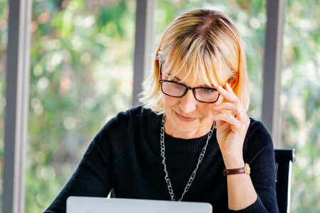 40s senior Caucasian businesswoman concentrating and staring at computer laptop in office environment