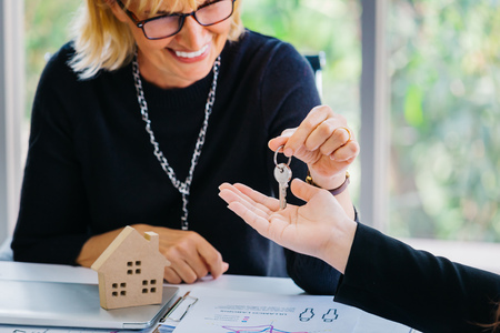 Adult businesswoman smiling and giving key to crop hand while sitting at desk with house model in office of real estate agency Banco de Imagens