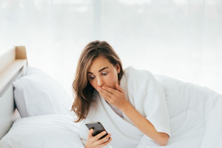 Wondered young woman with hand near mouth seeing late time on mobile phone on bed in morning Stock Photo