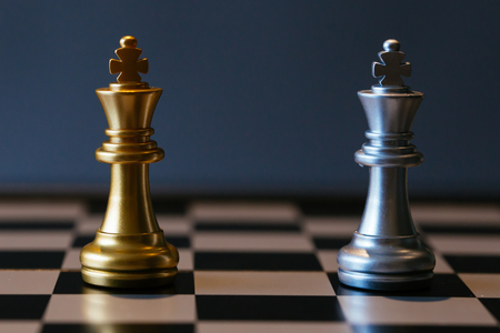 Close up shot of golden and silver chess kings placed against each other on chessboard