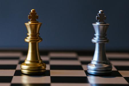 Primer plano de reyes de ajedrez de oro y plata colocados uno contra el otro en el tablero de ajedrez