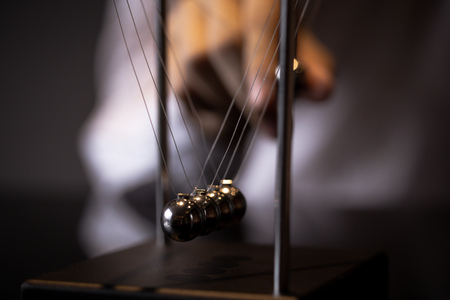 Unrecognizable blurred male pulling ball of metal Newton cradle and observing momentum